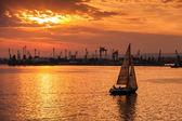 Sailing yacht enters Varna harbor at the sunset — Stock Photo
