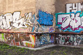 Abandoned courtyard with colorful graffiti text — Stock Photo