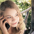 Teenage girl in a park talking on a cell phone — Stock Photo #72463455