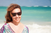 Young happy woman in sunglasses on ocean coast — Stock Photo