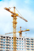 Two cranes work in modern houses massive — Stock Photo