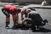 Asphalting in progress, workers install sewer manhole — Stock Photo