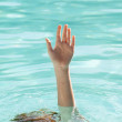 Hand of drowning person stretching out of water — Stock Photo #74104357