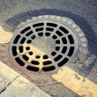 Urban pavement and sewer manhole cover — Stock Photo #74330729