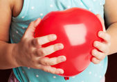 Baby holds red heart shaped balloon — Stock Photo