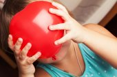 Baby girl holds small red heart shaped balloon  — Stock Photo