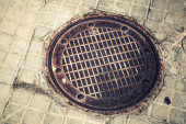 Round rusted hatch in urban pavement — Stock Photo