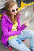 Blond teenager girl with a lollipop — Stock Photo