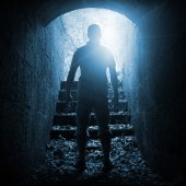 Young man stands in dark stone tunnel, blue toned — Stock Photo