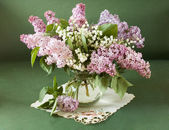 Still life with lilac flowers and lily of the valley in vase isolated on artistic background — Stock Photo