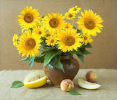 Still life with sunflowers and fruits on artistic background — Stock Photo