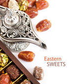 Eastern sweet (still life with nuts, candy, metal vase and date isolated on white background) — Stock Photo