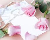 Zátiší s bandou čajové růže, hedvábí, perl náhrdelník a pohár na umělecké zázemí — Stock fotografie