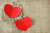 Valentine's Day (red paper hearts pined on sacking background ) — Стоковое фото