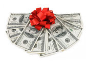 Money gift (big stack of dollars with red bow isolated on white background) — Stock Photo