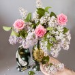 Still life with roses and lilac flowers bunch on silver tea tray on artistic background — Stock Photo #64682725