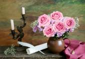 Artistic still life with roses bunch, candles, manuscript and old pen on painting background — Stock Photo