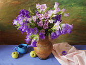 Still life with bluebells bunch, pot and apples s on artistic background — Stock Photo