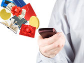 Modern mobile phone in the hand with lots of goods isolated on white (e-shopping concept) — Stock Photo