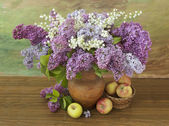 Still life with lilac flowers and apple — Stock Photo