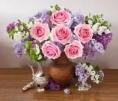Still life with huge bunch of roses, lilac flowers on painting background — Stock Photo