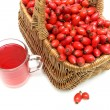 Wicker basket with berries of wild rose and a drink in a glass m — Stock Photo #53936297