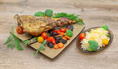 Roasted leg of lamb with vegetables and herbs on a wooden backgr — 图库照片
