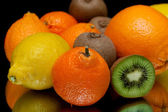 Mandarin and other fruits closeup on black background — Stock Photo