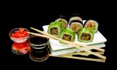 Japanese rolls, soy sauce and pickled ginger on a black backgrou — Stock Photo
