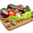 Fresh vegetables and quail eggs on a cutting board on a white ba — Stock Photo #74505377