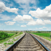 Railroad to horizon in green landscape and cloudy sky — Stock Photo