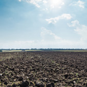 Sun in clouds over black field after harvesting — Stock Photo