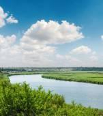 Blue sky with white clouds over river in green riverside — Stock Photo