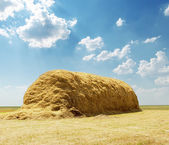 Stack of straw under blue sky with clouds — Stock Photo