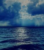 Dramatic sky with clouds over dark sea — Stock Photo
