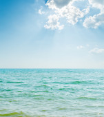 Blue sea and clouds in sunrays — Stockfoto