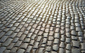 Cobbled road as background on sunset — Stock Photo
