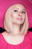 Beautiful blond woman with makeup, smiling girl posing in pink h — Stock Photo