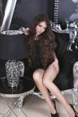 Beautiful brunette girl model in short black dress posing on lux — Stock Photo