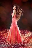 Glam linda com cabelos longos, posando em vestido vermelho sobre bokeh bri — Fotografia Stock