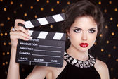 Fashion elegant woman with sexy red lips holding cinema clap. Su — Stock Photo