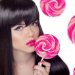 Attractive pretty girl with pink lips holding lollipop over swee — Stock Photo #60974973