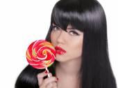 Young sensual girl sucking lollipop. Red lips. Makeup. Brunette  — Stock Photo