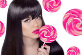 Attractive pretty girl with pink lips holding lollipop over swee — Stock Photo