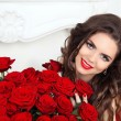 Beautiful smiling woman with makeup, red roses bouquet of flower — Stock Photo #61707131
