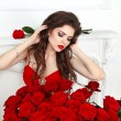 Beauty model girl with makeup, long hair and beautiful red roses — Stock Photo #61707175