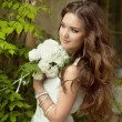 Beautiful smiling bride with wedding bouquet of flowers at park. — Stock Photo #71535015