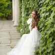 Outdoor Portrait Of Beautiful bride in white wedding dress in gr — Stock Photo #71535065