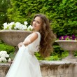 Attractive Gorgeous bride with long wavy hair in wedding dress a — Stock Photo #71535071