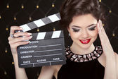 Fashion elegant woman posing with sexy red lips holding cinema c — Stock Photo